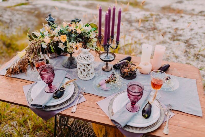 Деревянный стол послужен для 2, на таблице там составы цветков, свечей, столового прибора и стекел для вина стоковое изображение