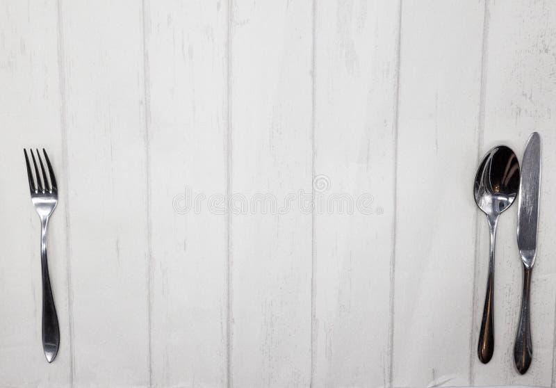 Деревянный стол стиля Провансали, предпосылка для меню, бистро, кафа, ресторана Нож, вилка, ложь ложки на светлой деревянной пред стоковое изображение