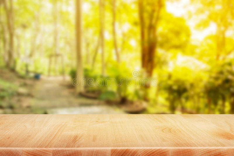 Деревянный стол столешницы в предпосылке утра сада - смогите быть используемым f стоковое изображение rf