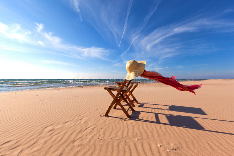 Деревянный стул на пляже с соломенной шляпой и шарфом стоковое изображение
