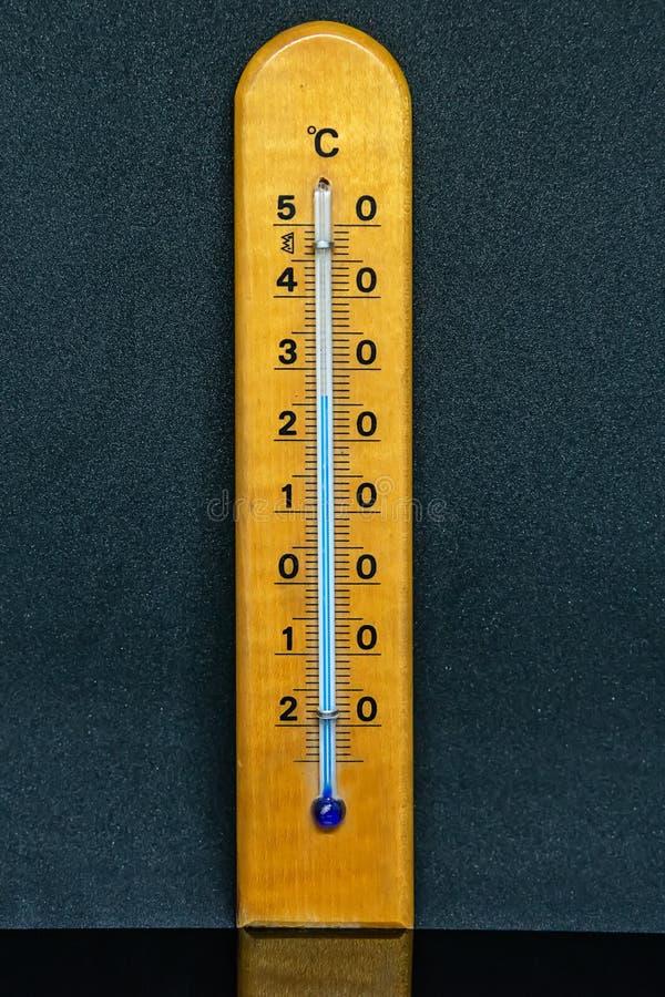 Деревянный термометр изолированный на черной предпосылке Деревянный изолированный термометр стоковые фотографии rf