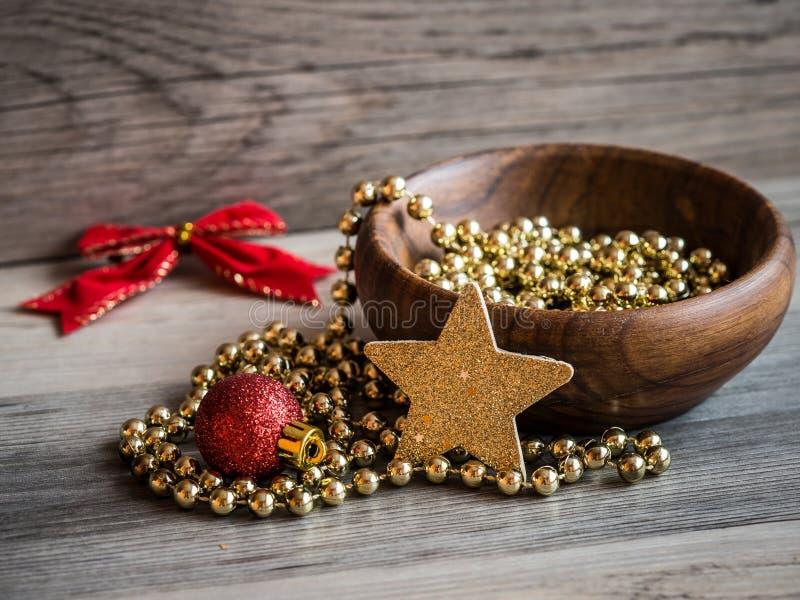 Деревянный шар с цепью жемчуга рождества золотой, красным орнаментом яркого блеска и золотой звездой с красным смычком стоковые изображения