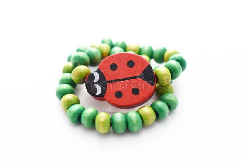 Деревянный Ladybug браслета шариков на белой предпосылке стоковое фото