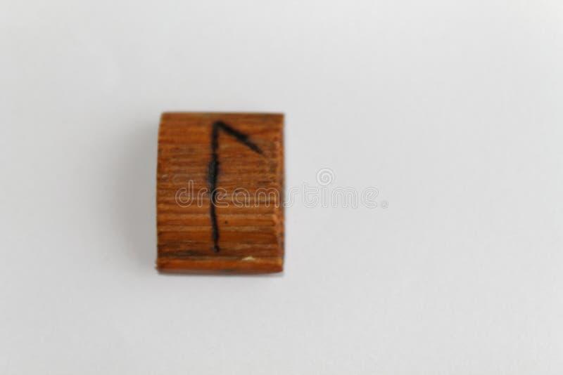 Деревянный rune который значит воду, озеро или по возможности лук-порей, ложь на таблице на белой предпосылке стоковые фотографии rf