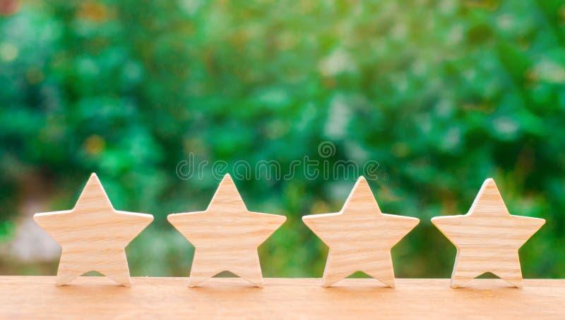 4 деревянных звезды Концепция оценки и оценки Оценка гостиницы, ресторана, передвижного применения Качественный сервис, стоковые фотографии rf