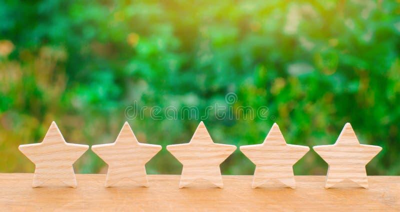 5 деревянных звезд Получите пятую звезду Концепция оценки гостиниц и ресторанов, оценка критиков и посетители стоковая фотография