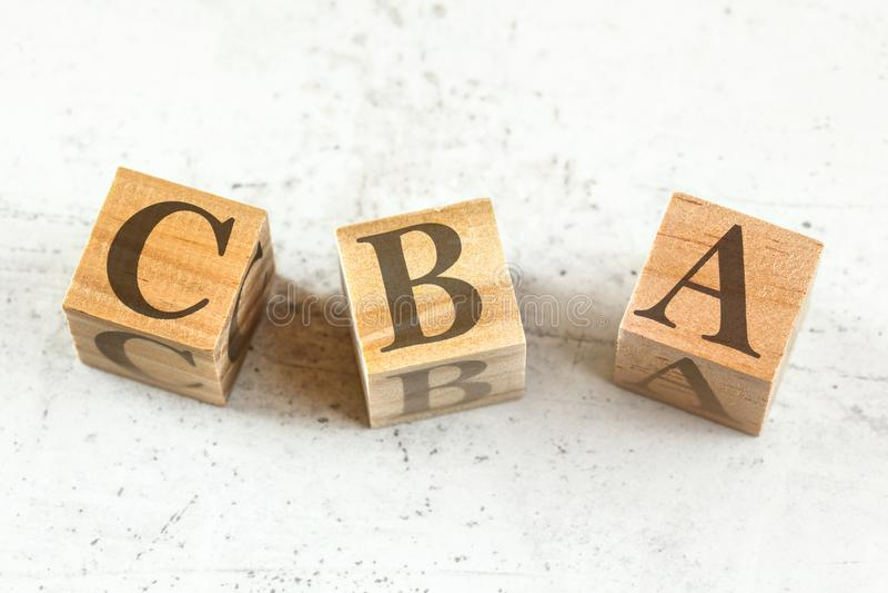 3 деревянных куба с письмами CBA стоят для стоить оценки преимущества на белой доске стоковое фото rf