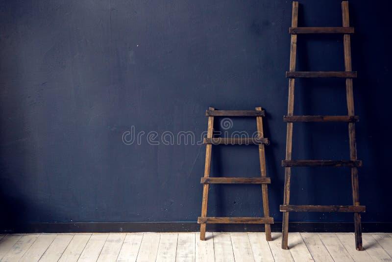 2 деревянных лестницы стоят на голубой стене на белом поле стоковые изображения