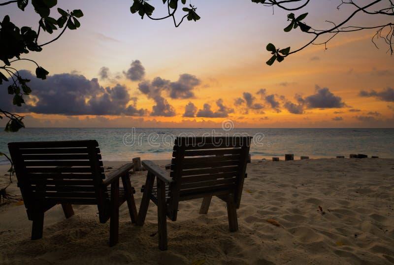 2 деревянных стуль на тропическом пляже во время захода солнца, низкого ключевого света стоковые изображения rf