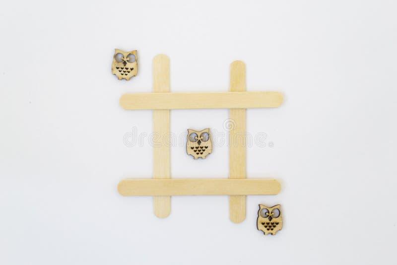 3 деревянных сыча лежат в ряд в линии в игре tic-tac-пальца ноги, в решетке на белой предпосылке стоковое изображение rf
