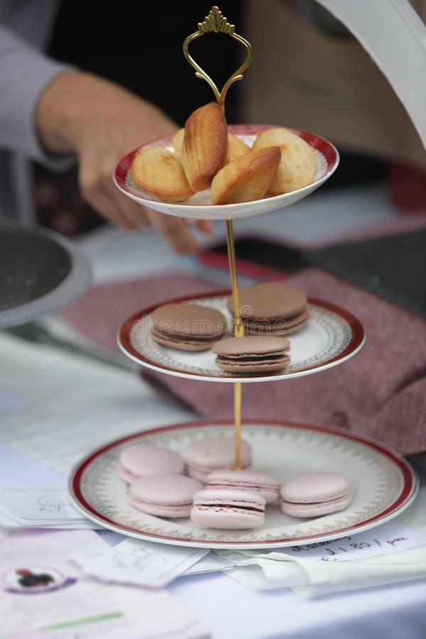Держатель стойла указывая на macaroons и другие помадки на стойке торта 3 ярусов стоковое изображение