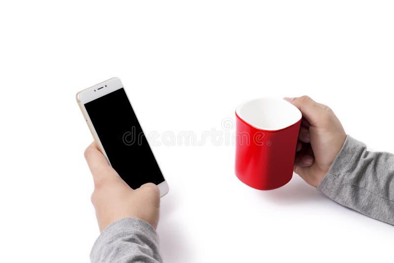 Держать белый телефон и красную чашку стоковые фотографии rf