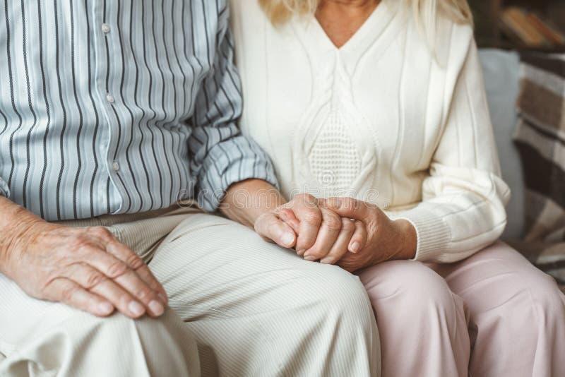 Держать старшей концепции выхода на пенсию пар совместно дома сидя вручает конец-вверх стоковое фото