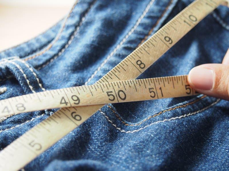 Держать tapeline на талии джинсов стоковые изображения rf
