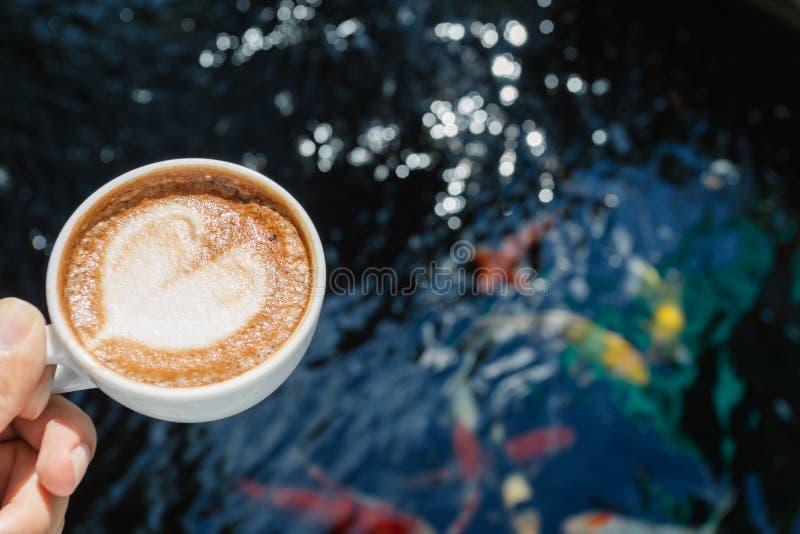 Держащ горячую чашку кофе см. koi стоковая фотография
