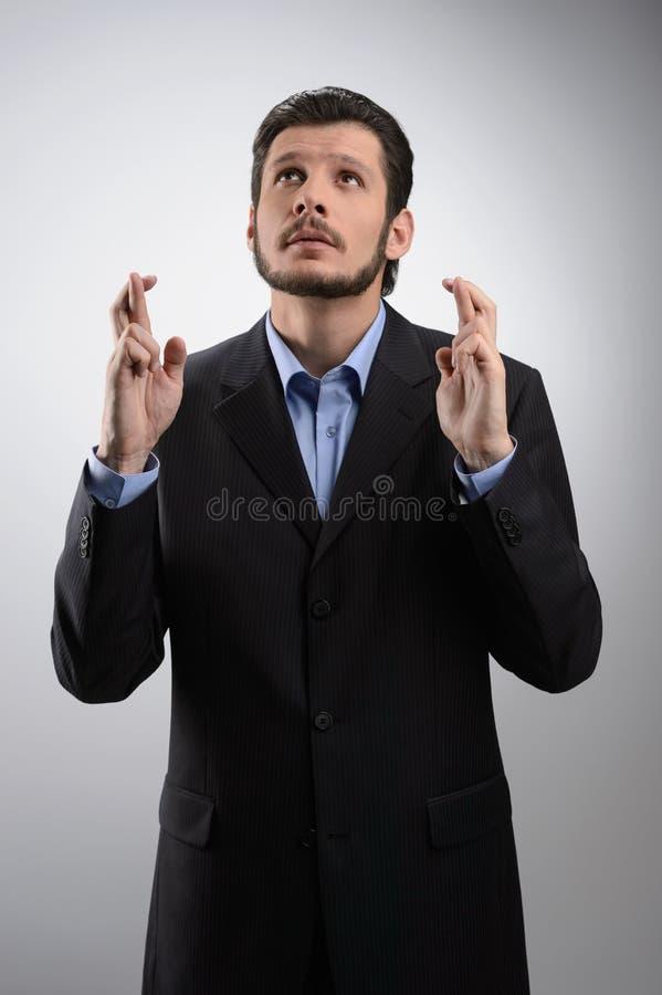 Держащ его пальцы пересеченный. Бизнесмен стоя с его finge стоковые фото