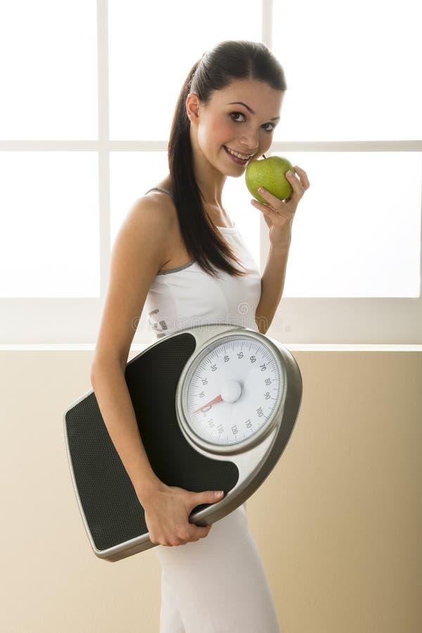 держащ женщину веса маштаба молодой стоковое изображение rf