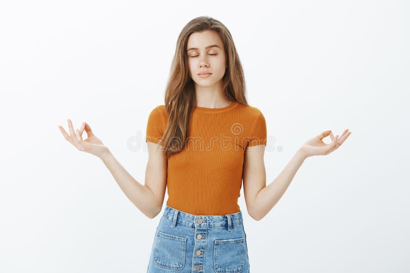Держащ разум здоровый Спокойная симпатичная стильная женщина при светлые волосы, закрывая глаза и положение ослабленные над серым стоковые изображения