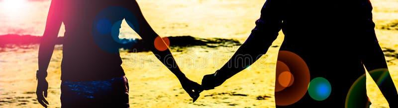 Держащ руки против захода солнца сверх стоковое изображение rf