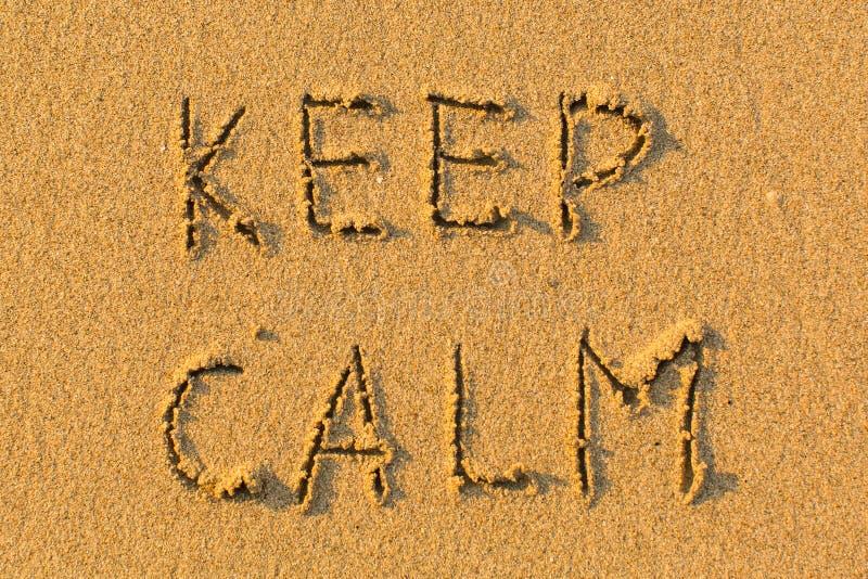 ДЕРЖИТЕ ЗАТИШЬЕ - слова рукописные на пляже песка Аннотация стоковая фотография rf