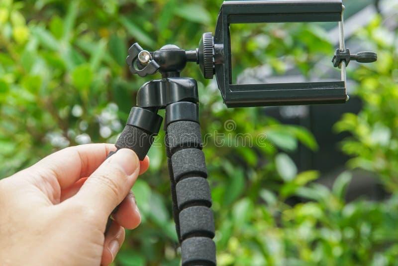 Держите треногу для мобильного телефона для фотоснимок с зеленым фоном природы стоковые фотографии rf