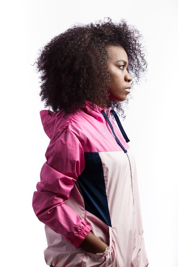 Дерзкая молодая курчавая коричнев-с волосами девушка одетая в розовой куртке спорта стоит на белой предпосылке в студии стоковое изображение