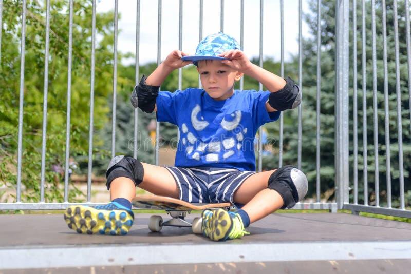 Дерзкий молодой мальчик сидя на его скейтборде стоковое изображение