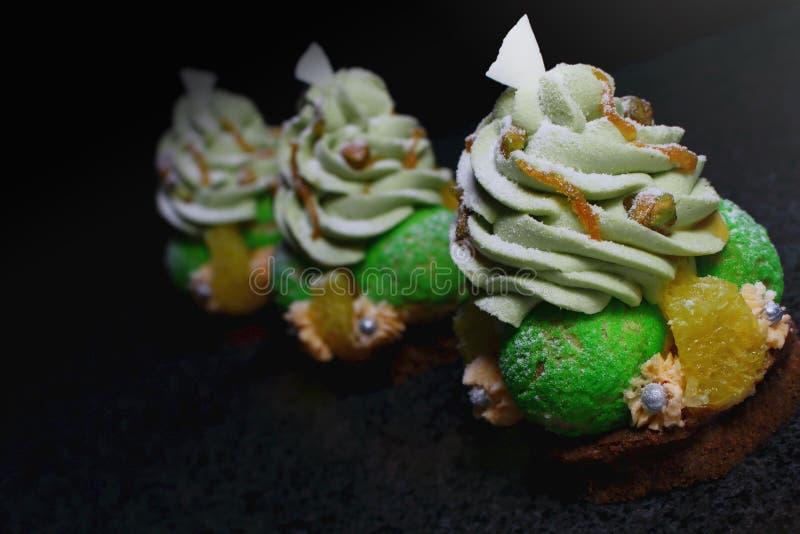 Десерты печенья choux рождественской елки с апельсинами, ganache фисташки и белыми украшениями шоколада стоковые изображения rf
