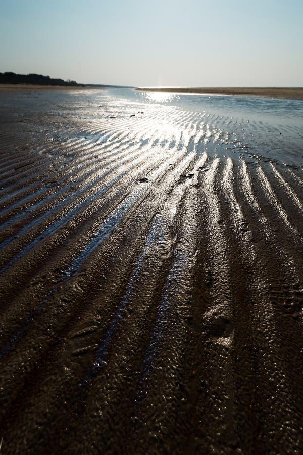 Десерт как текстурированный песок - пляж залива Балтийского моря с белым песком в заходе солнца стоковые фото