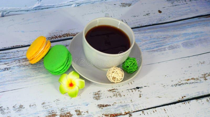 Десерт на завтрак, чашка кофе и 2 macaroons, оформление шариков ротанга и бутон цветка : стоковые изображения