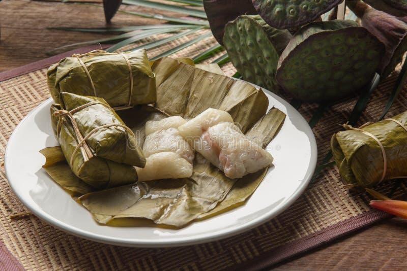 Десерт стиля Тайской кухни Khao Tom сумашедший, сделанный из банана и glutinous риса, обруч с лист банана на деревянном столе стоковые фотографии rf