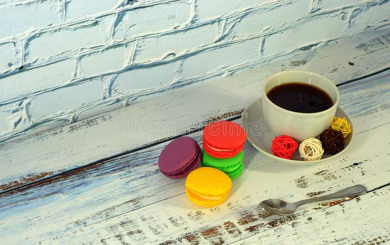 Десерт, чашка черного кофе и 4 macaroons других цветов : стоковое изображение rf