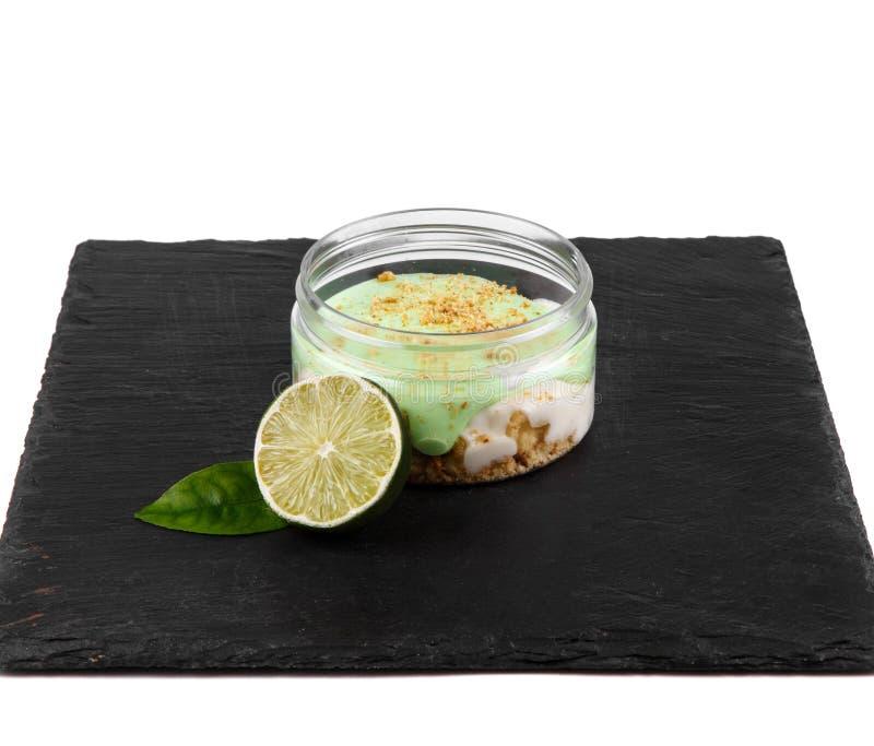 Десерт чизкейка известки в опарнике на черной каменной плите на белой предпосылке стоковая фотография