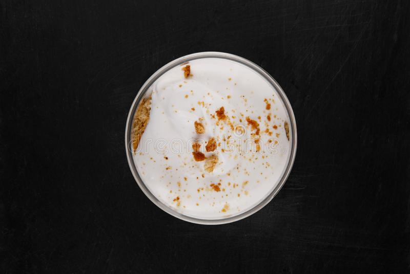 Десерт чизкейка меда в опарнике на черной каменной плите на белой предпосылке стоковые изображения