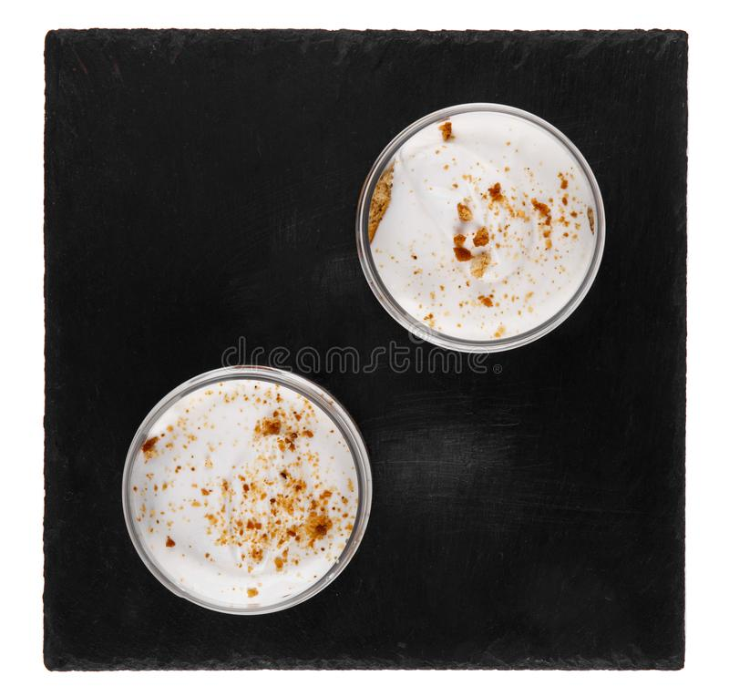 Десерт чизкейка меда в опарнике на черной каменной плите на белой предпосылке стоковое изображение