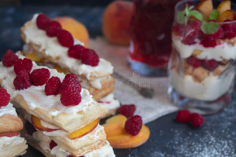 Десерт Milfey Прокладки печенья слойки с ягодами поленики сливк творога и кусками персика стоковое фото