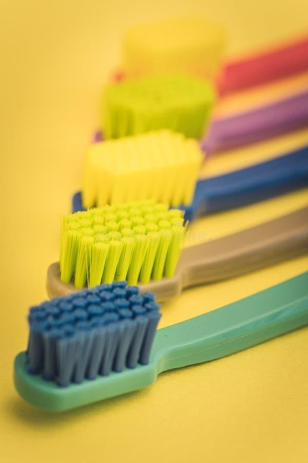 Детализированный близко вверх различных покрашенных зубных щеток в дантисте стоковое изображение