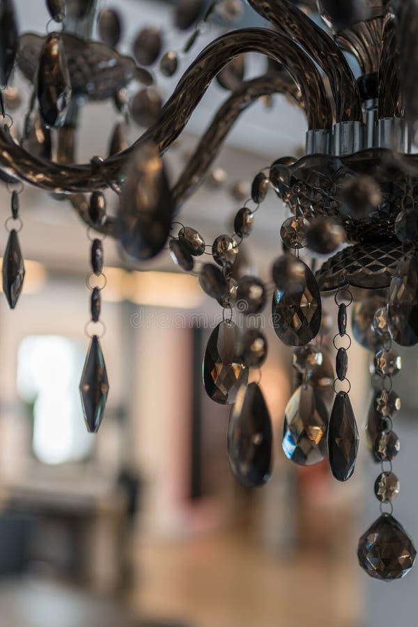 Детали стеклянной люстры с запачканной комнатой на заднем плане стоковое фото rf