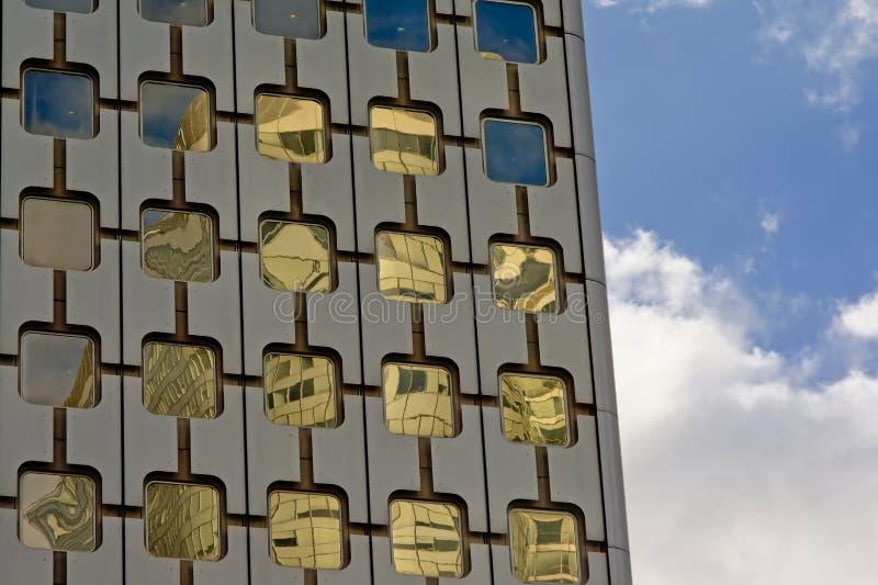 Деталь архитектуры, окна с округленными углами офисного здания и голубое небо с облаками стоковая фотография