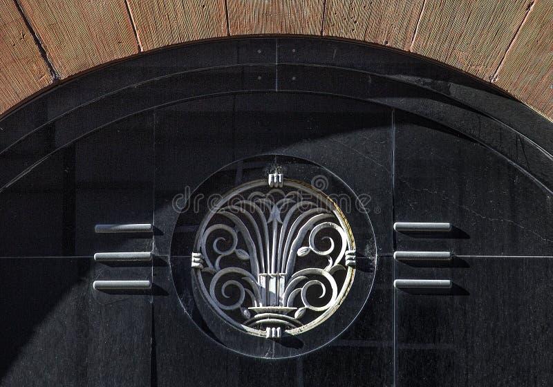 Деталь внешнего здания терракоты архитектурного стиля стиля Арт Деко с сводом входа и эмблемы металла на черном grainite стоковое фото rf