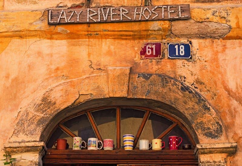 Деталь входа в ленивое общежитие реки в исторической части городка Loket Различные чашки стоят на полке над парадным входом стоковое изображение rf