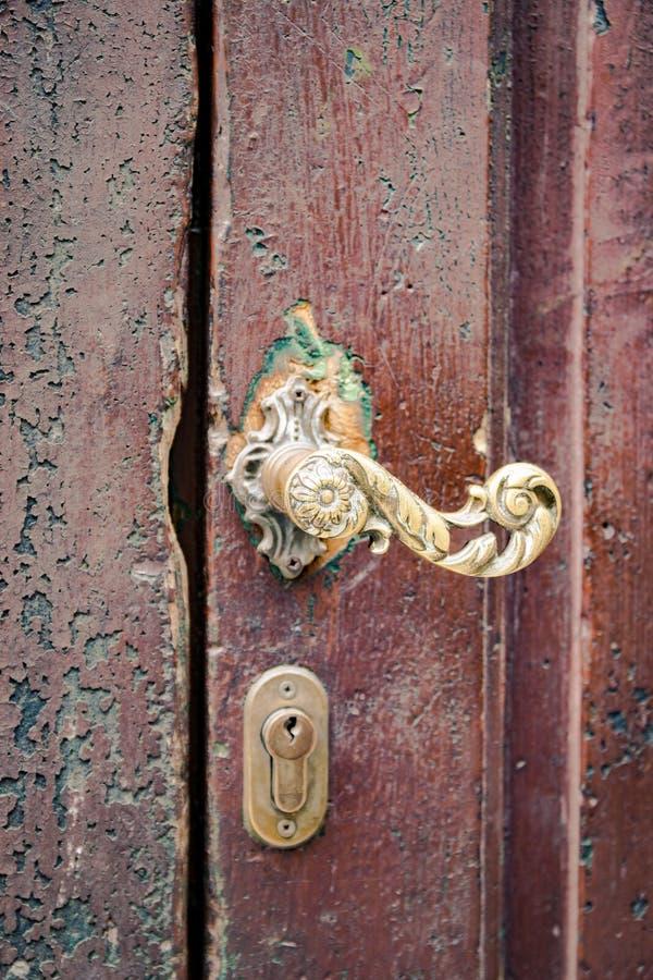 Деталь позолоченной ручки металла старой деревянной двери стоковое изображение