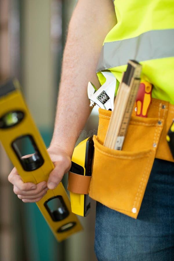 Деталь рабочий-строителя на поясе инструмента строительной площадки нося стоковое изображение rf