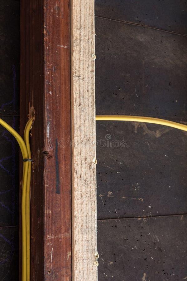 Деталь реновации конструкции старого стержня стены и нового sistered стержня с желтой электрической проводкой и черной бумагой см стоковые фотографии rf