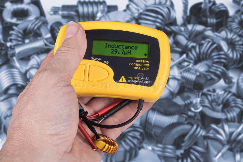 Деталь руки с цифровым метром электрических пассивных компонентов стоковые фотографии rf