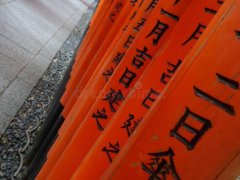 Деталь сочинительств на красных воротах Torii на святыне Fushimi Inari в Киото стоковые фотографии rf