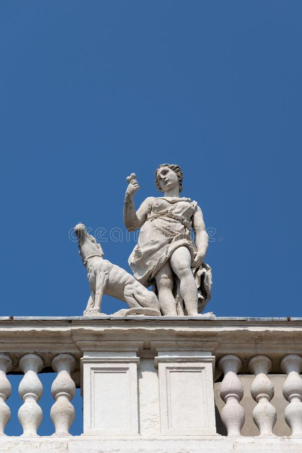 Деталь статуи от крыши Palazzo Canossa, Corso Cavour, Вероны, женской диаграммы держа вне косточку к собаке стоковые изображения rf