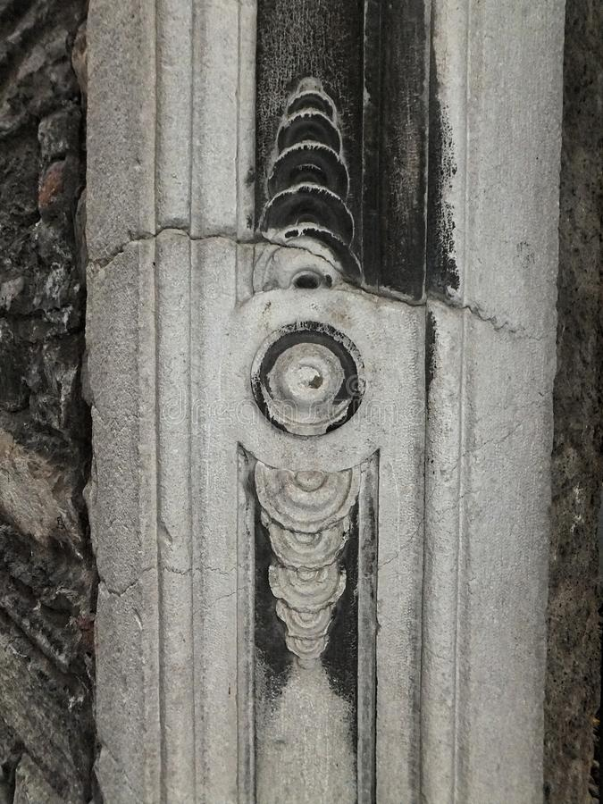 Деталь угла наружной стены в улице Como, Италии Белый врем-выдержанный камень, треснутый и отчасти очерненный с сажей стоковая фотография