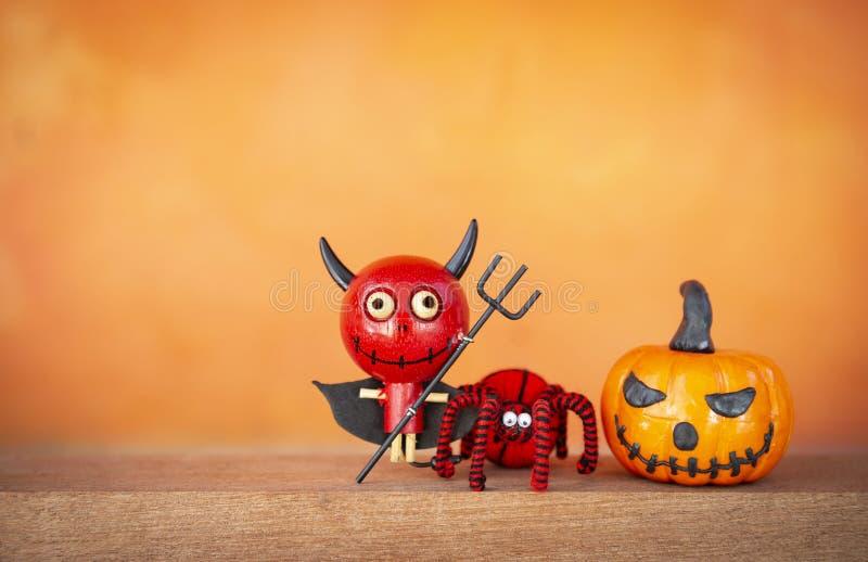 Деталь украшения хеллоуина, милый красный дьявол и смешная тыква с черным и красным пауком стоковое изображение