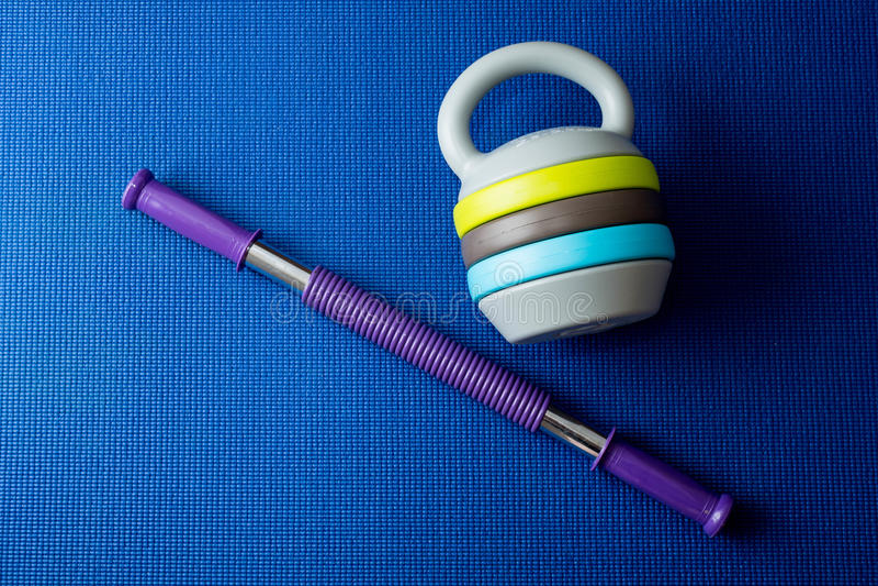 Детандер и регулируемое kettlebell на голубой предпосылке циновки йоги стоковая фотография